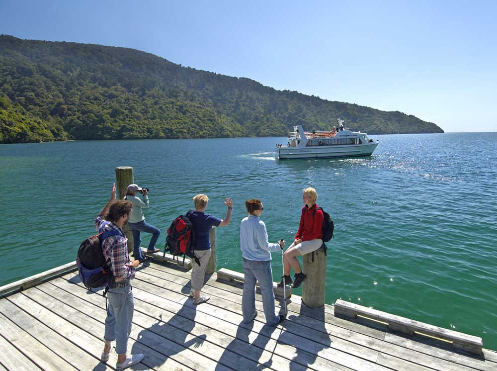 Walkers waiting for a water taxi in the Marlborough Sounds