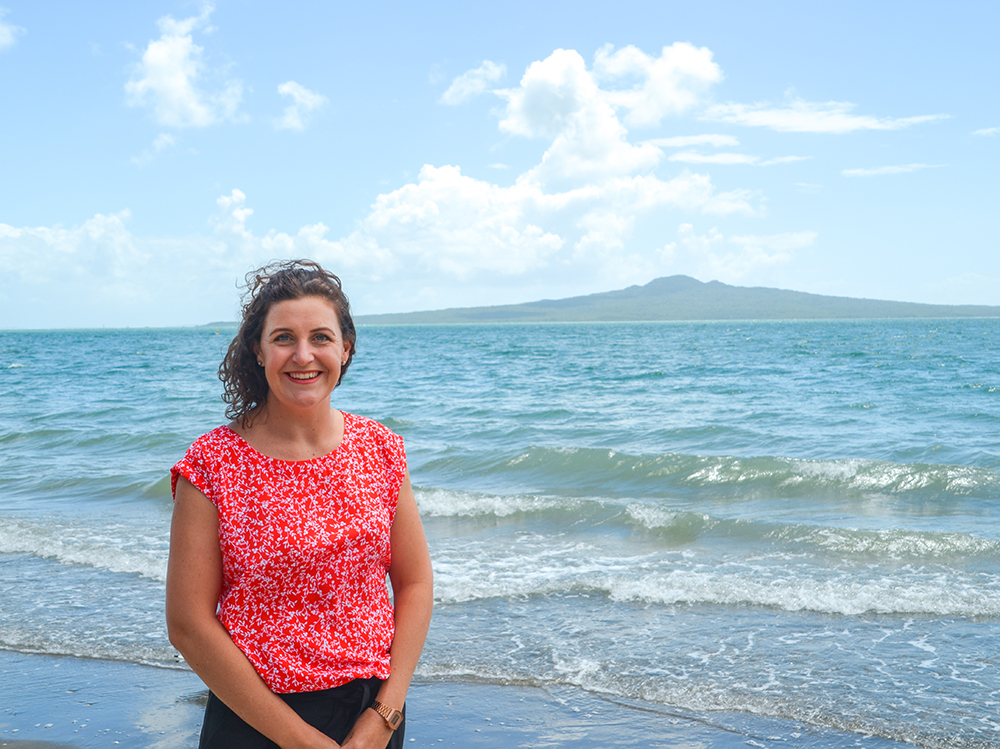 Alisha from MoaTours on the beach at Mission Bay, Rangitoto Island in the background