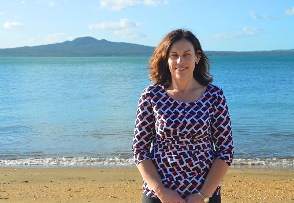 Tanya from MoaTrek on the beach in Auckland, Rangitoto Island behind