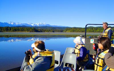 Guide and guests on Okarito Lagoon wildlife cruise