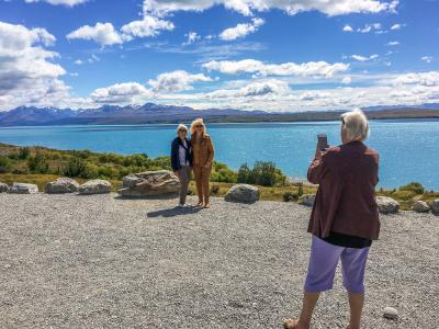 Travellers making a photo stop at Lake Pukaki, Mt Cook region