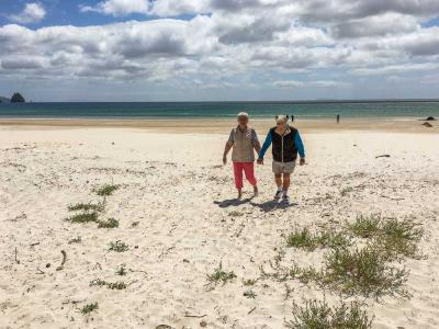 Couple walking hand in hand on Whangapoua Beach, Coromandel